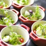 Na petit casserole coloquei o bacalhau, alho e cebola confitados, tomate cereja, ovo de codorna, azeitona preta, ervilhas, ceboulete e manjericão em flor.