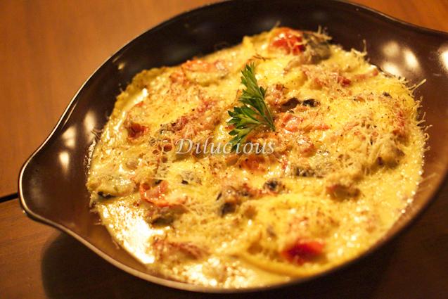 Ravioli di Capra (ravioli caseiro recheado com queijo de cabra com mix de cogumelos frescos, prosciutto crudo e tomate cereja)