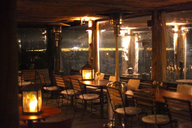 Na espaço exterior, deck de madeira com iluminação a base de muita vela
