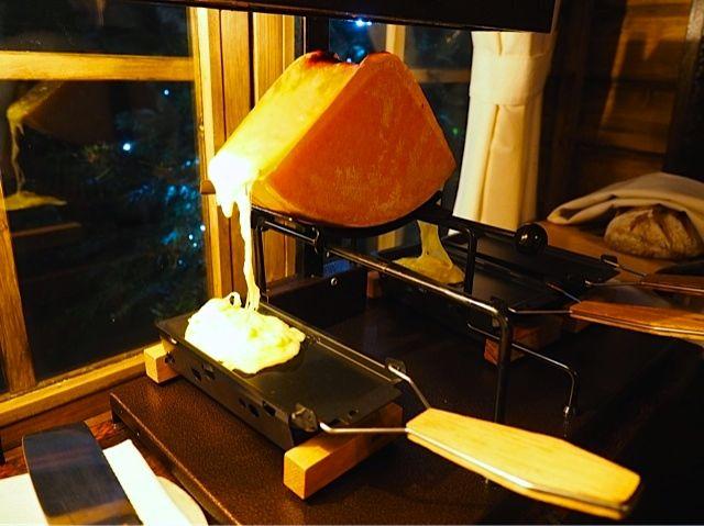 Graças ao calor da racleteira, o queijo vai derretendo e fica pronto par ser colocado em cima de batatas cozidas.