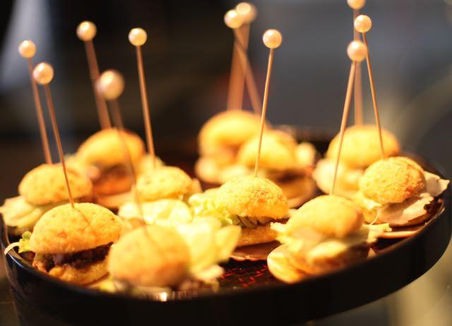 Pãezinhos de Queijo recheados com Pernil, alface americana, uma fatia de tomate e mostarda.